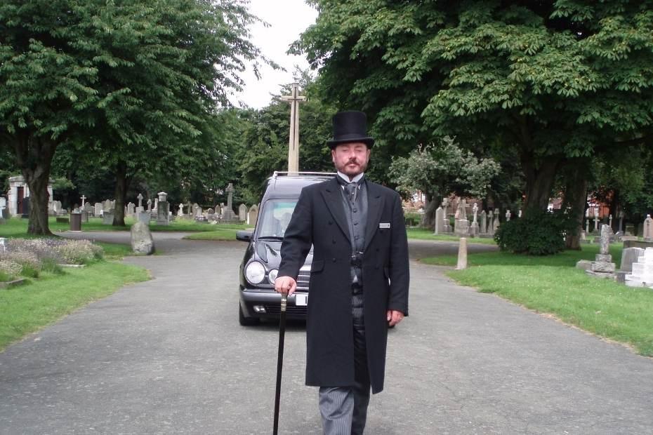 Funeral director walking ahead of hearse